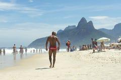Mięśniowy Młody Brazylijski mężczyzna Chodzi Ipanema plażę zdjęcia stock