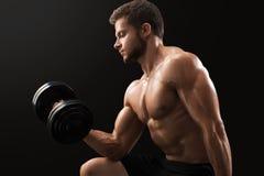 Mięśniowy młody człowiek ćwiczy z dumbbells fotografia stock