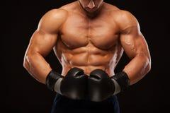 Mięśniowy młody człowiek z perfect półpostacią z sześć paczek abs w bokserskich rękawiczkach, pokazuje różnych strajki i ruchy Zdjęcie Royalty Free
