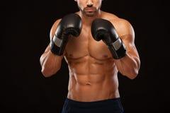Mięśniowy młody człowiek z perfect półpostacią z sześć paczek abs w bokserskich rękawiczkach, pokazuje różnych strajki i ruchy fotografia royalty free