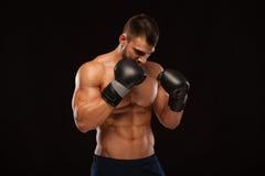 Mięśniowy młody człowiek z perfect półpostacią z sześć paczek abs w bokserskich rękawiczkach, pokazuje różnych strajki i ruchy Obrazy Royalty Free