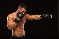 Mięśniowy młody człowiek z perfect półpostacią z sześć paczek abs w bokserskich rękawiczkach, pokazuje różnych strajki i ruchy Zdjęcia Royalty Free