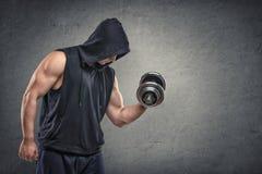 Mięśniowy młody facet podnosi dumbbell pokazywać jego bicepsy w hoodie Fotografia Stock