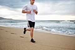 Mięśniowy młody jogger bieg na plaży wzdłuż morza Obrazy Royalty Free