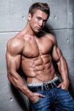 Mięśniowy młody seksowny facet pozuje w cajgach i chested