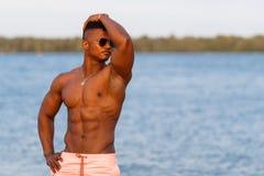 Mięśniowy młody sportowy seksowny mężczyzna na plaży z nagą półpostacią w bieliźnie Gorący czarny piękny facet, sprawność fizyczn Obraz Stock
