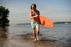 Mięśniowy plażowy ratownika bieg wzdłuż brzeg rzeki z życiem Obraz Stock