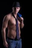 Mięśniowy seksowny mężczyzna pozuje w krawacie z kapeluszem na czarnym backgrou, Zdjęcie Royalty Free