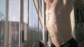 Mięśniowy silny sportowiec trenuje brzusznych mięśnie na barze w gym podczas władza treningu w w górę światła słonecznego zbiory wideo