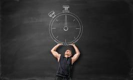 Mięśniowy sportowiec trzyma up dużego zegar, rysującego na blackboard Fotografia Stock