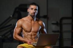 Mięśniowy Sportowy Bodybuilder sprawności fizycznej modela Use komputer obrazy stock