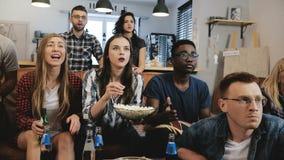 Międzykulturowy grupowy zegarek bawi się grę na TV Namiętni zwolennicy świętują cel z napojami 4K zwolnionego tempa zakończenie U fotografia royalty free