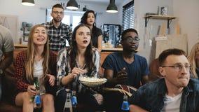 Międzykulturowy grupowy zegarek bawi się grę na TV Namiętni zwolennicy świętują cel z napojami 4K zwolnionego tempa zakończenie U fotografia stock