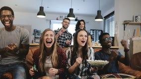 Międzykulturowy grupowy zegarek bawi się grę na TV Namiętni zwolennicy świętują cel z napojami 4K zwolnionego tempa zakończenie U zdjęcie stock