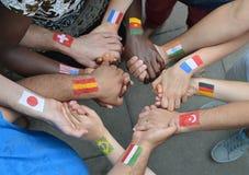 Międzynarodowi ludzie trzyma ręki z flaga Zdjęcie Stock