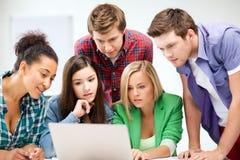 Międzynarodowi ucznie patrzeje laptop przy szkołą Obrazy Royalty Free