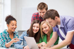 Międzynarodowi ucznie patrzeje laptop przy szkołą fotografia stock