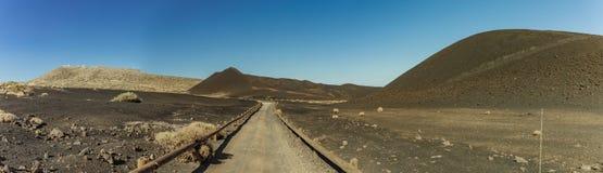 Międzynarodowy obserwatorium w Teide parku narodowym Wiejska droga biega w czarnych volcanoes w przedpolu Wietrzny dzień z jaskra zdjęcie stock