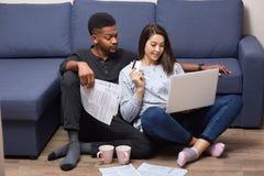 Międzyrasowa para młodzi ludzie siedzi wpólnie w frontowym laptopie na podłogowej pobliskiej kanapie w ich mieszkaniach, ruchliwi obraz royalty free