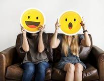 Międzyrasowe kobiety trzymający ekspresyjnych emoticons Obraz Royalty Free