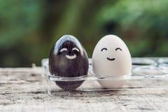 Międzyrasowego małżeństwa pojęcie Czarny i biały jajko jako para różne rasy fotografia stock