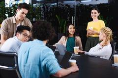 międzyrasowi partnery biznesowi z papierowymi filiżanka kawy ma spotkania przy stołem z laptopami w nowożytnym obraz royalty free