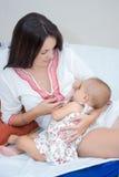 Miękcy fotografii potomstwa matkują żywieniową pierś jej dziecko Zdjęcia Stock