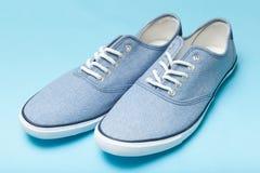 Miękcy wygodni błękitni sneakers na błękitnym tle zdjęcia stock