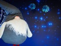 Miękka elf zabawki pozycja przeciw gwiaździstemu zmrokowi - błękitny tło fotografia stock
