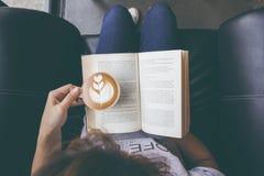 Miękka fotografia czyta książkę i pije kawę młoda dziewczyna, wierzchołek zdjęcia royalty free