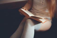 Miękka fotografia kobieta na łóżkowej czytelniczej książce Kobieta w kneesocks na ciemnym tle z książką obrazy stock