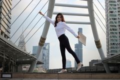 Miękka ostrość pomyślna młoda Azjatycka biznesowa kobieta podnosi jej ręki z dokument falcówką przy miastowym budynku tłem obrazy stock