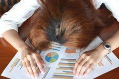 Miękka ostrość zmęczona zapracowana młoda biznesowej kobiety chyłu puszka głowa na mapach w biurze zdjęcie royalty free