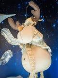 Miękka renifer zabawki pozycja przeciw gwiaździstemu zmrokowi - błękitny tło zdjęcie stock