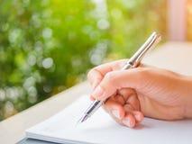Miękki ostrości kobiety ręki writing, biznesowy dokument i nutowa książka, Zdjęcia Stock