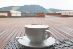 Miękki ostrości zakończenie w górę filiżanki capuccino latte kawa na drewnianym backgr obrazy stock