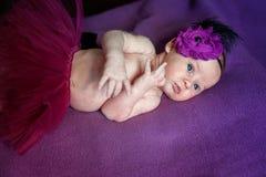 Miękki portret pokojowy słodki nowonarodzonego niemowlaka dziecka lying on the beach na łóżku podczas gdy śpiący w purpurowej koc zdjęcie stock