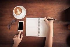 Miękki, rozmyty i odgórny widok, nastolatek ręka, pisze ołówkowego właściciela, telefonu komórkowego macanie, czerni przestrzeń d obrazy stock