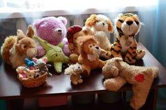 Miękkich części zabawki na stole Mokietu psi próbować dostawać z stołu oddalonych bieg i Obrazy Royalty Free