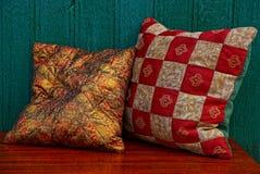 Miękkie poduszki na czerwień stole blisko zielenieją ścianę Zdjęcie Royalty Free