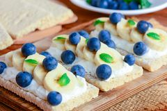 Miękkiego sera śmietanka, banany i jagod kanapki, Krakersa chleb z polewami na drewnianej desce zbliżenie Obrazy Stock