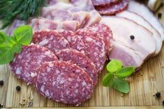 Mięsa salami, bekon i zielenie na tnącej desce -, Obraz Stock