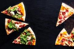 Mięsna pizza z rozciekłym mozzarella serem, pomidorem na czarnym st i Zdjęcia Royalty Free