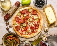 Mięsna pizza z składnikami wokoło sera, pepperoni, mięsa, oliwek, pieprzy, pieczarek i pikantność, Zdjęcia Royalty Free