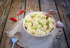 Mięsne kluchy - rosyjski gotowany pelmeni w talerzu Smażył łososia na talerzu z cytryną i koperem na błękitnym w kratkę stołowym  Zdjęcia Stock