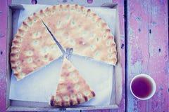 Mięsny kulebiak obok herbaty w kubku na ławce fotografia royalty free