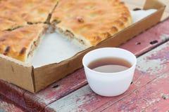 Mięsny kulebiak obok herbaty w kubku na ławce zdjęcie royalty free