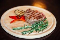Mięsny stek na drewnianym talerzu z bocznym naczyniem piec na grillu warzywa fotografia stock