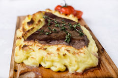 Mięsny stek z kartoflanym puree popierał na drewno desce Zdjęcie Royalty Free