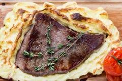 Mięsny stek z kartoflanym puree popierał na drewno desce Zdjęcia Royalty Free